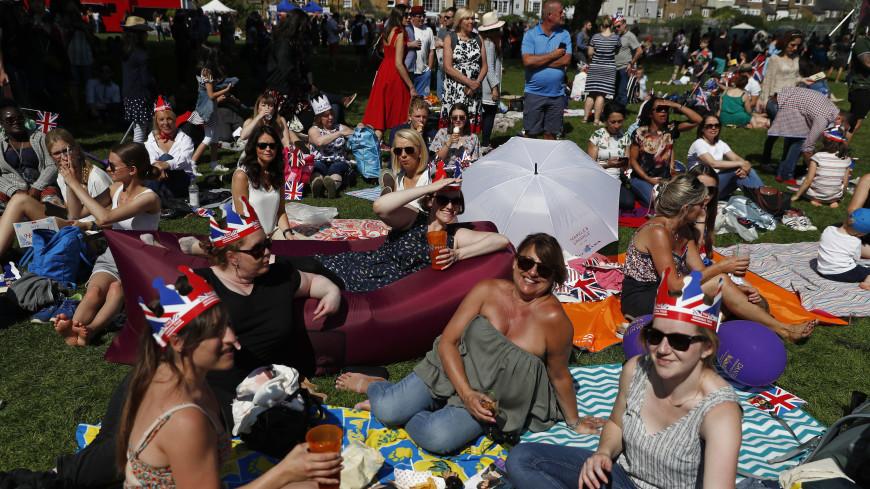 Тысячи людей в шляпках и с флажками празднуют свадьбу Гарри и Меган