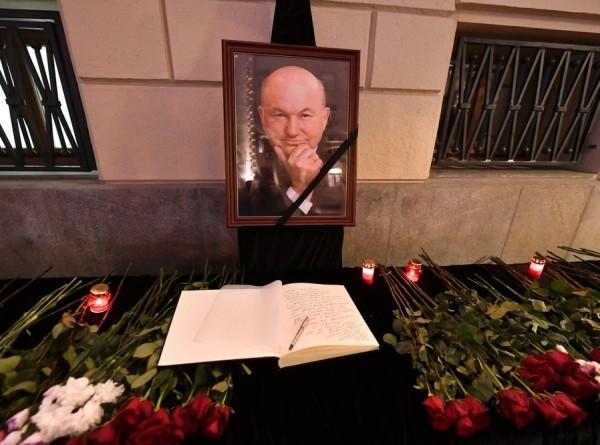 Москвичи несут цветы к мэрии в память о Лужкове
