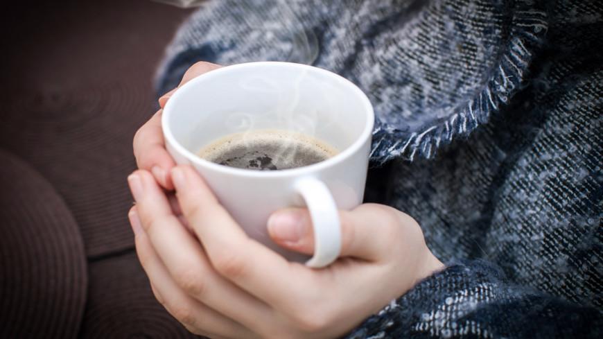 Чашка горячего кофе в руках молодой девушки