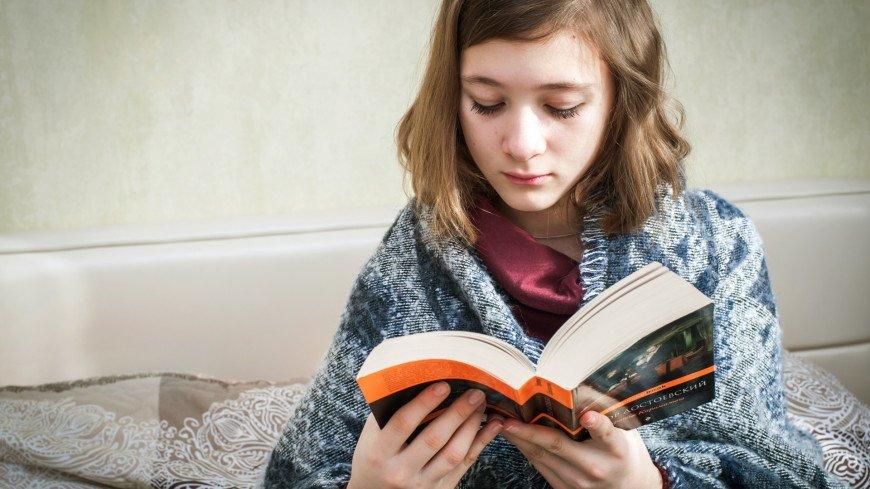 Молодая девушка читает книгу